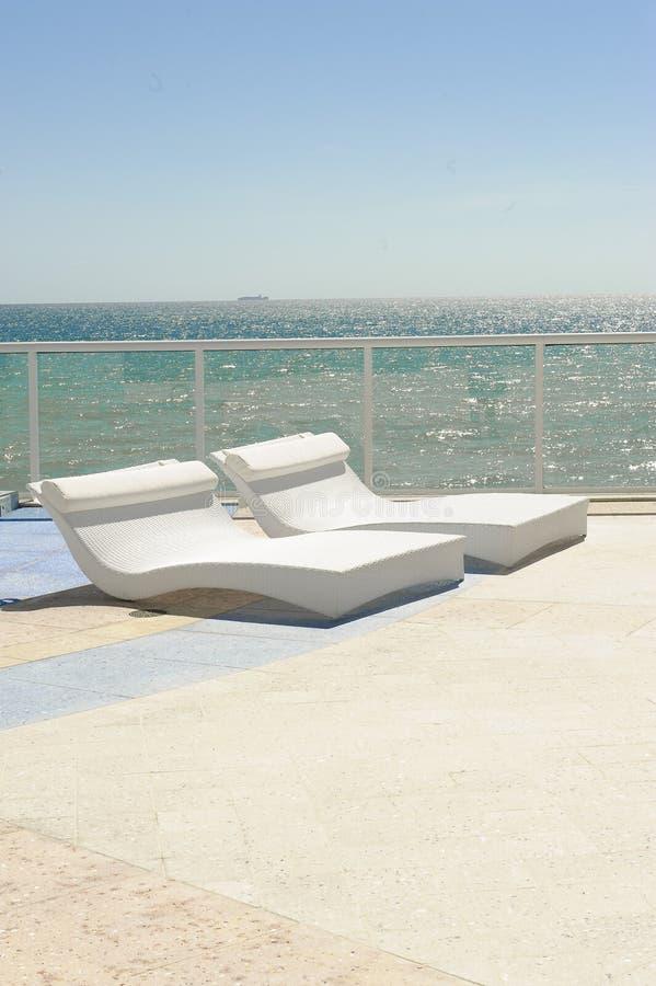 与椅子的热带海滩大阳台 免版税库存照片