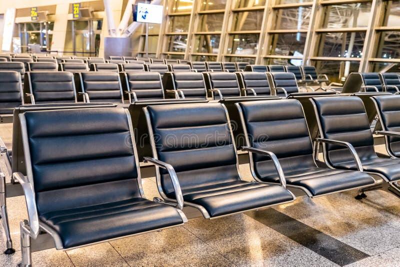 与椅子的空的机场终端等候室在晚上 免版税库存照片