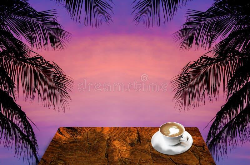 与椰子树剪影的饮料热的咖啡 库存照片