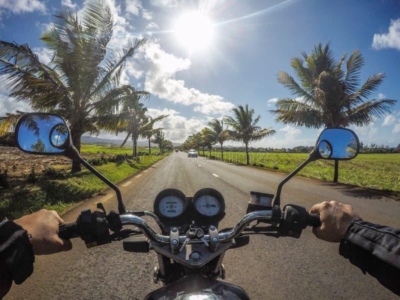 与椰子树贝耳Ombre毛里求斯的摩托车乘驾 库存照片