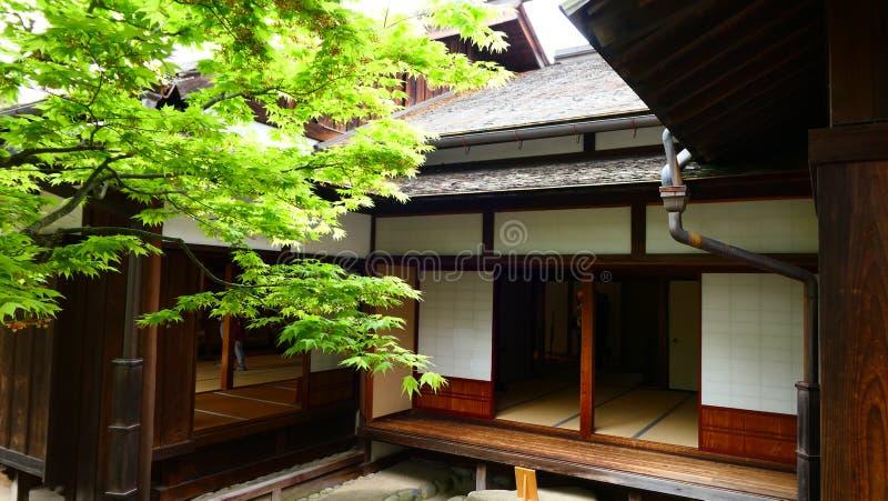 与槭树的日本老木大厦在庭院里 免版税库存照片