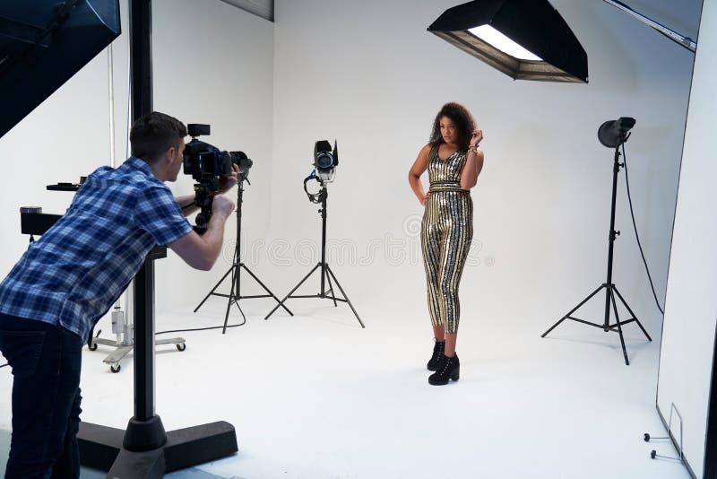 与模型的摄影师工作在时尚射击在演播室 免版税库存照片
