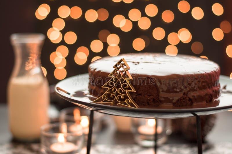 与模糊的圣诞灯的巧克力蛋糕。 免版税库存照片