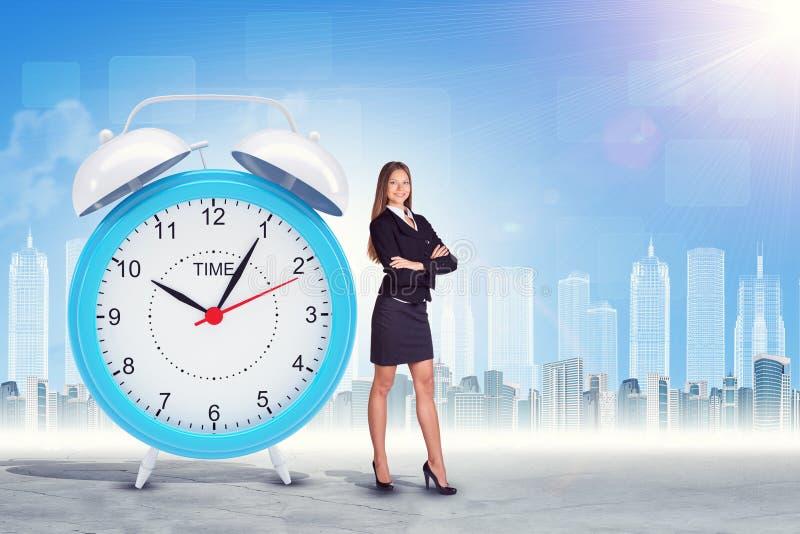 与横渡的胳膊和大时钟的Buisnesswoman 图库摄影