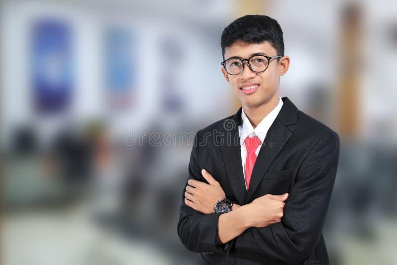 与横渡的胳膊的亚洲年轻商人身分 有胳膊的偶然商人横渡了 愉快的商人 免版税库存图片
