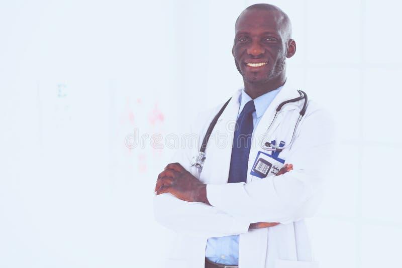 与横渡的胳膊的愉快的非洲的人医生画象 库存照片