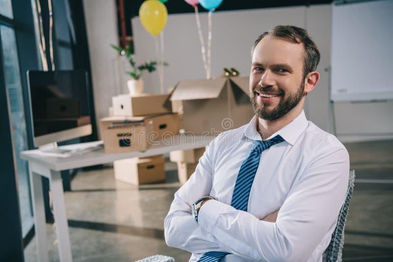 与横渡的胳膊的英俊的商人微笑对照相机的在装饰的新的办公室 库存照片