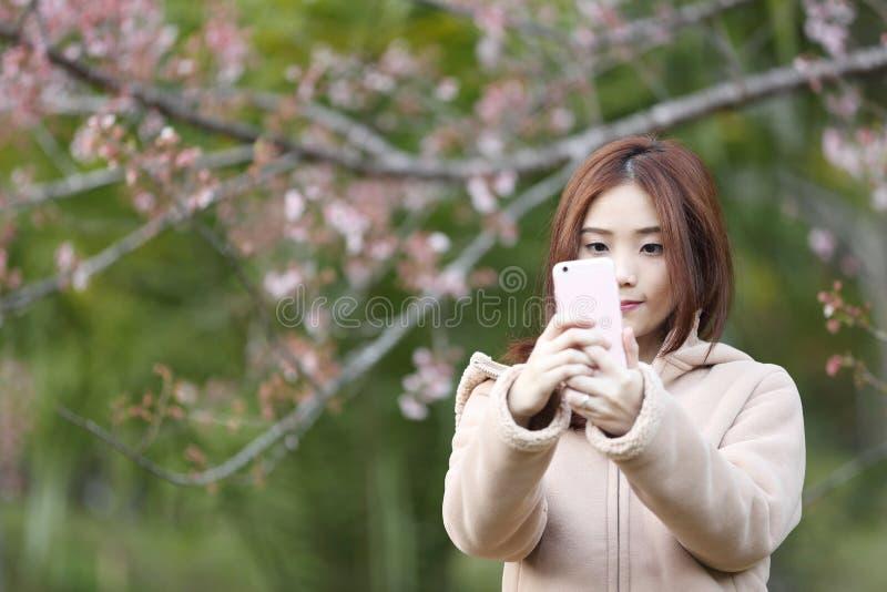 与樱花佐仓的亚洲妇女selfie 库存照片