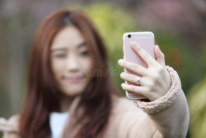 与樱花佐仓的亚洲妇女selfie 图库摄影