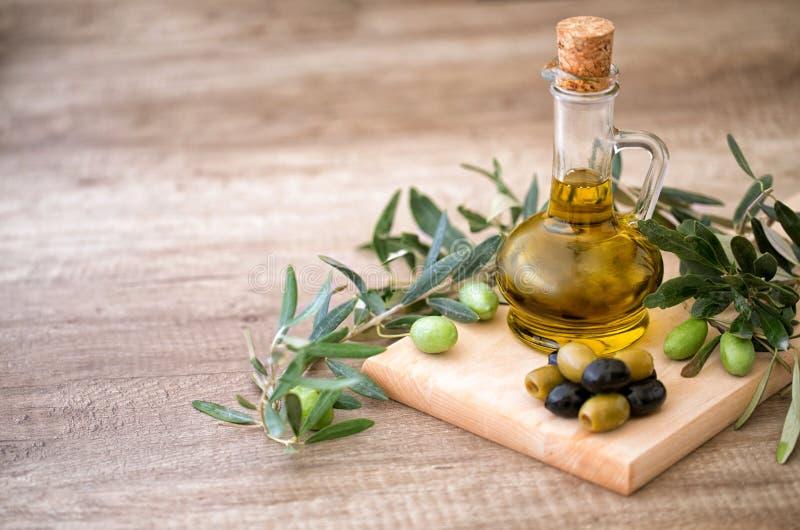 与橄榄树枝和瓶的绿色和黑橄榄橄榄色的oi 免版税库存照片