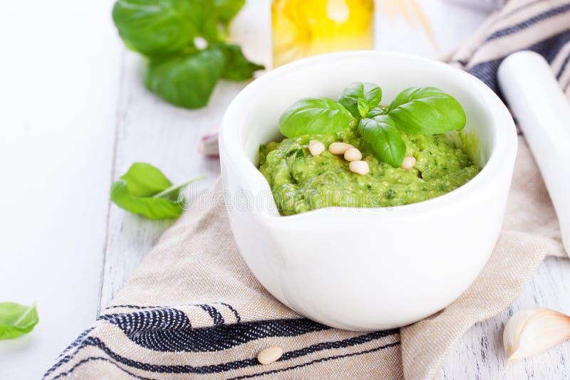 与橄榄油、松子和大蒜的自创传统蓬蒿pesto在一张木土气桌上的一个白色碗 图库摄影