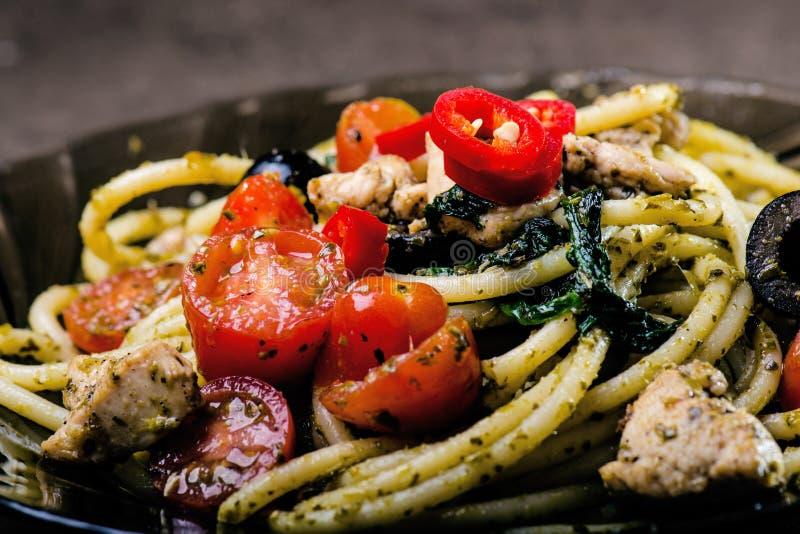 与橄榄油、蕃茄,草本,冷颤的意粉面团和被削减的鸡胸脯意大利人烹调 板材用在一张黑桌上的食物 免版税图库摄影