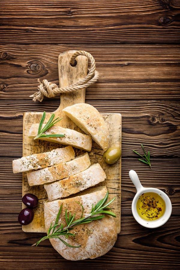与橄榄油和橄榄的可口自创意大利ciabatta面包在木土气背景,在看法上,文本的空间 免版税库存图片