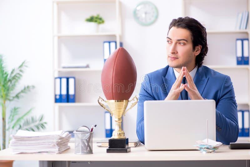 与橄榄球球的年轻英俊的商人在办公室 图库摄影