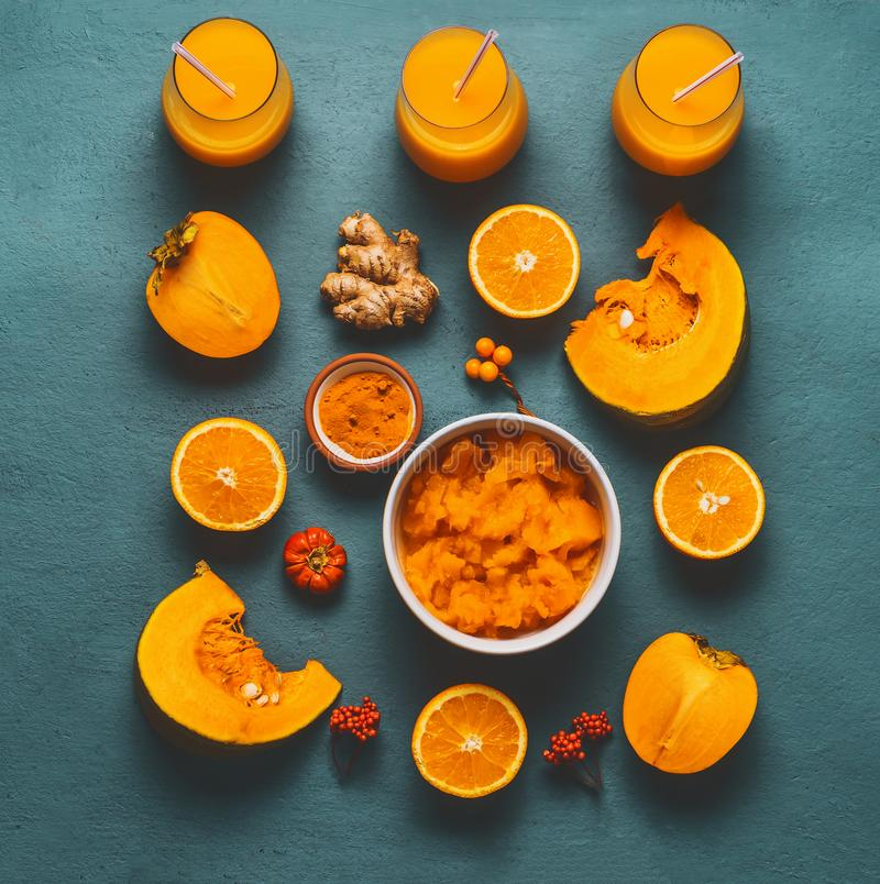 与橘黄色成份的健康南瓜圆滑的人:柿子,橙色果子、姜和姜黄粉末 库存图片