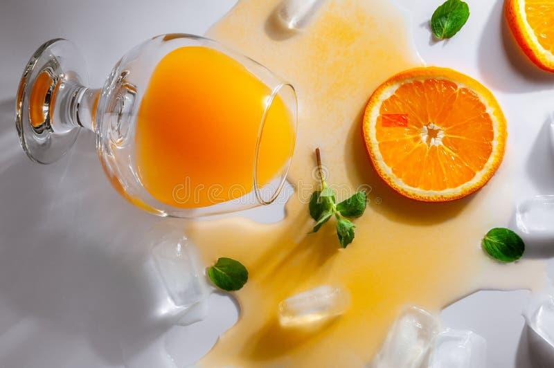 与橙汁过去谎言的一块被翻转的玻璃在一张白色桌上 汁液延长了表面 在玻璃附近是冰块,桔子 库存照片