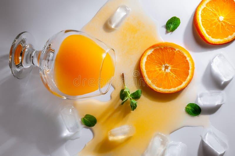 与橙汁过去谎言的一块被翻转的玻璃在一张白色桌上 汁液延长了表面 在玻璃附近是冰块,桔子 免版税库存照片