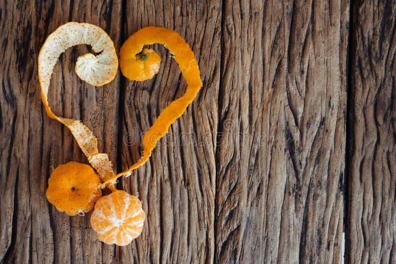 与橙皮的心脏在木背景 库存照片