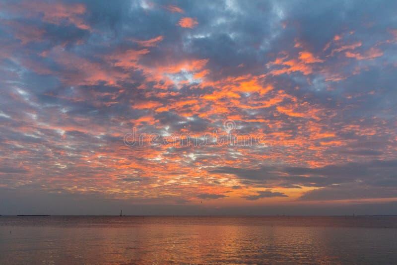 与橙色云彩和遥远的小船的日落天空 图库摄影