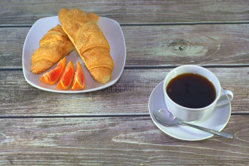 与橙色切片的两个新月形面包在板材和一个杯子在一个茶碟的无奶咖啡有在桌上的一把匙子的 r 免版税库存照片