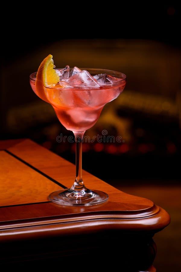 与橙色切片的内格罗尼鸡尾酒在与燃烧的壁炉的经典古板的木桌上在背景中 库存图片