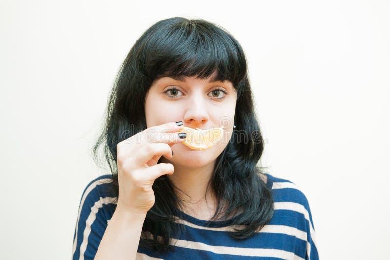 与橙色切片的微笑的深色的女孩戏剧 免版税库存照片
