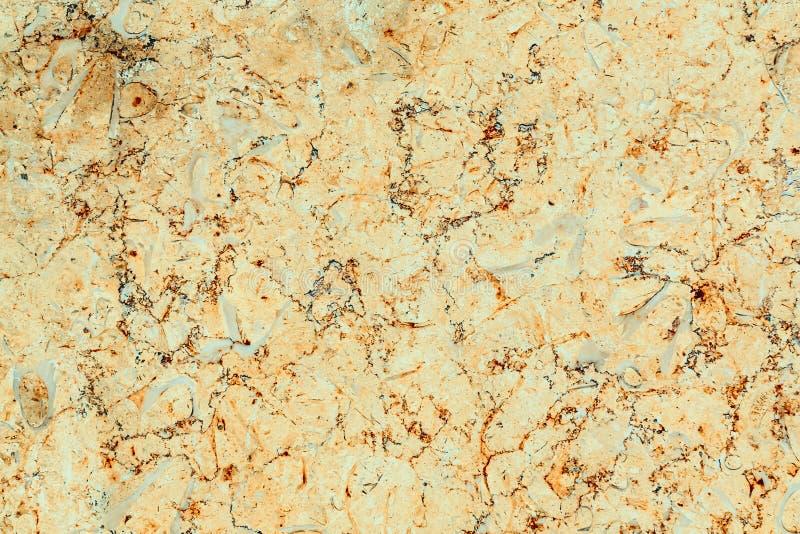 与橙色和灰色条纹,纹理的被擦亮的黄色大理石 免版税库存图片