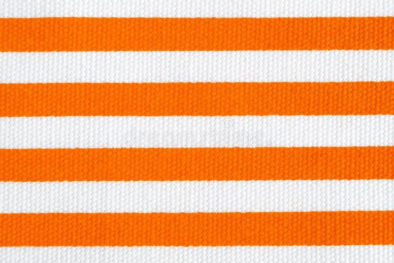 与橙色和白色条纹的纺织品背景 织品纹理 免版税库存照片