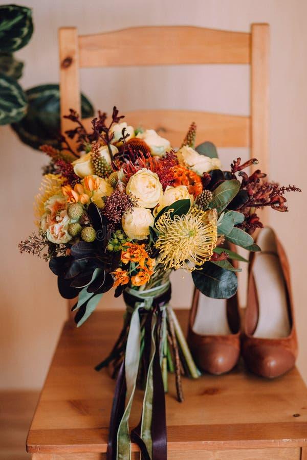 与橙色和黄色花的美丽的秋天婚礼花束在红色鞋子旁边的一把木椅子 免版税库存图片
