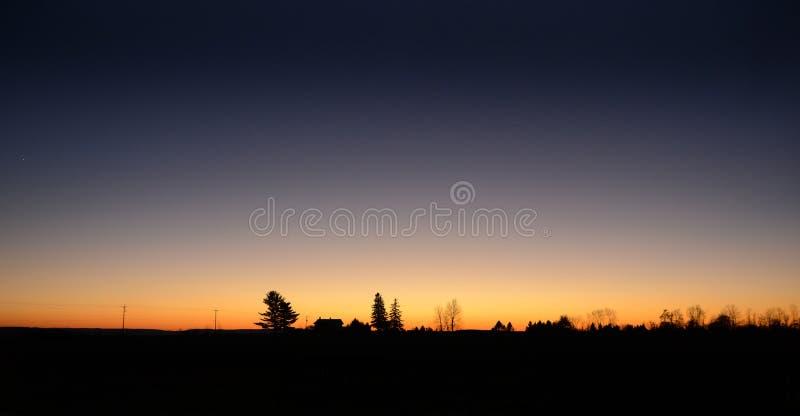 与橙色日落现出轮廓的风景的清楚的天空 免版税图库摄影