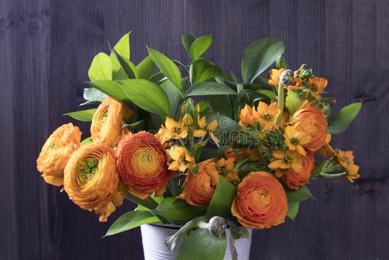 与橙色毛茛属和万年青在木背景的Dubium的婚礼花束 免版税图库摄影