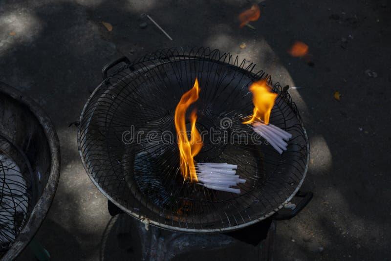 与橙色火的白色蜡蜡烛在金属碗 宗教标志燃烧的蜡烛 白色烛光焰 库存图片
