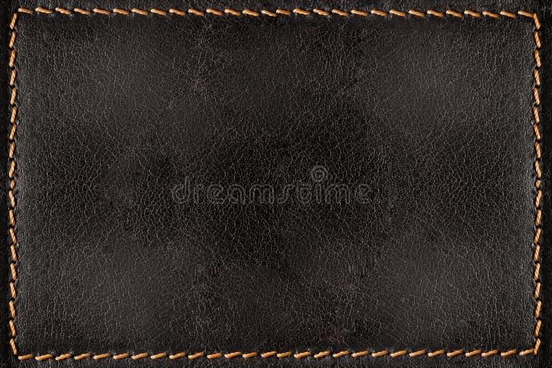 与橙色缝的黑皮革纹理背景 免版税库存照片