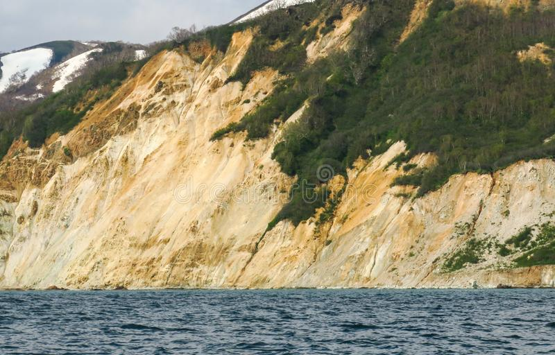 与橙黄色色的沙子石灰石岩石和地质结构在岸,在温暖的完善的远征的令人惊讶的海岸线 库存照片