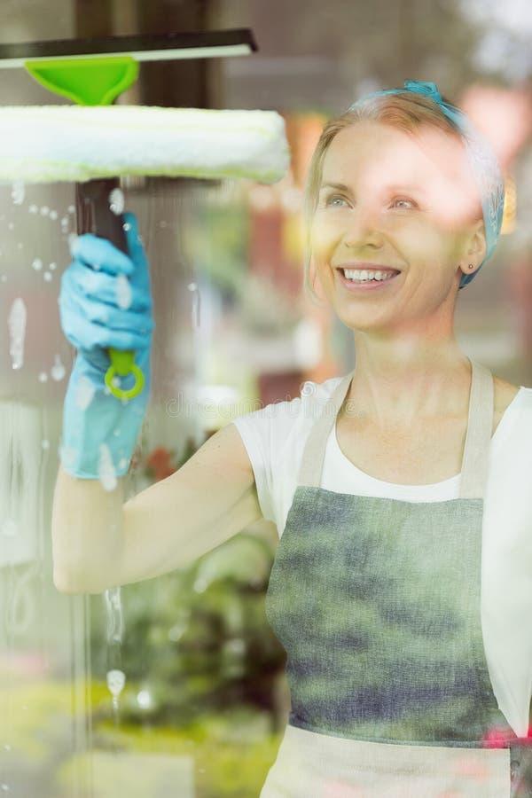 与橡皮刮板的主妇洗涤的窗口 库存图片