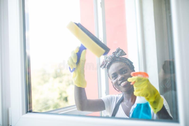 与橡皮刮板的微笑的年轻美国黑人的妇女清洗的玻璃窗 图库摄影