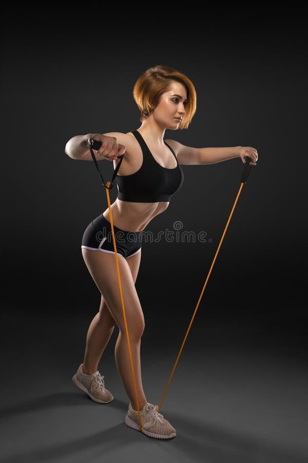 与橡胶抵抗带的有吸引力的强的妇女锻炼 免版税图库摄影
