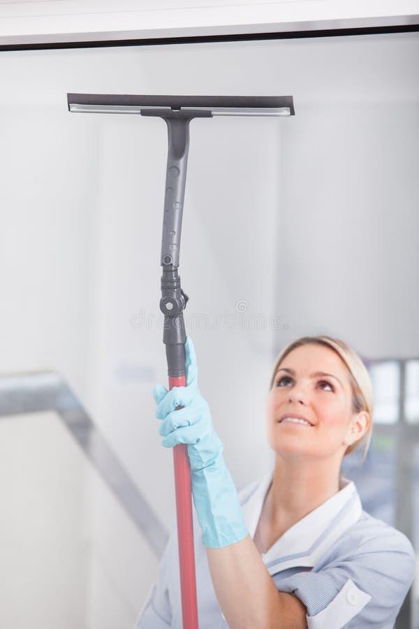 与橡胶风窗清洁器的妇女清洁 免版税库存照片