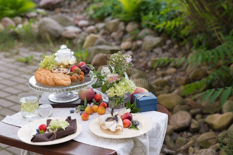 与欢乐款待的表和桌布在夏天庭院里 免版税库存图片