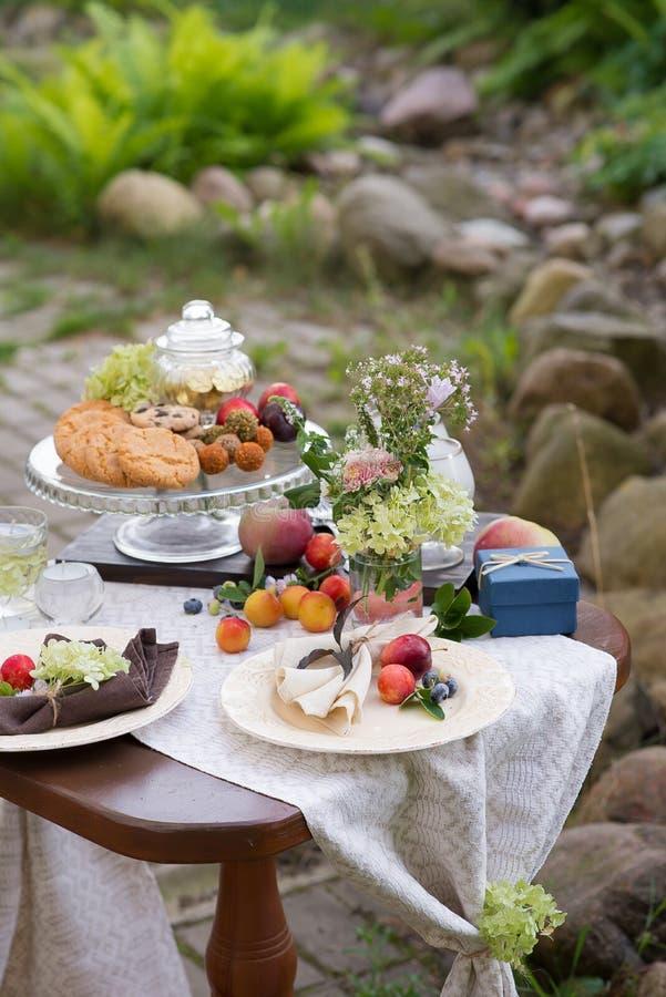 与欢乐款待的表和桌布在夏天庭院里 库存图片