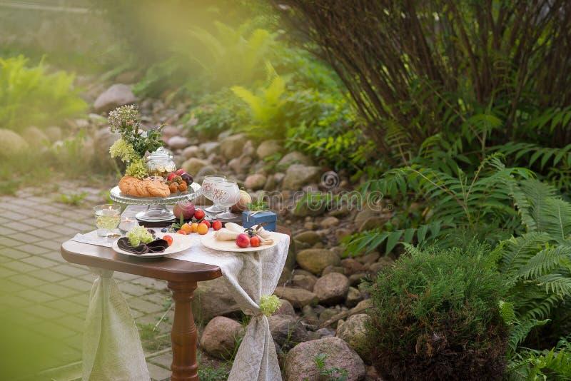 与欢乐款待的表和桌布在夏天庭院里 免版税库存照片