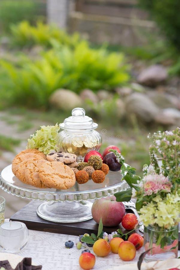 与欢乐款待的表和桌布在夏天庭院里 库存照片