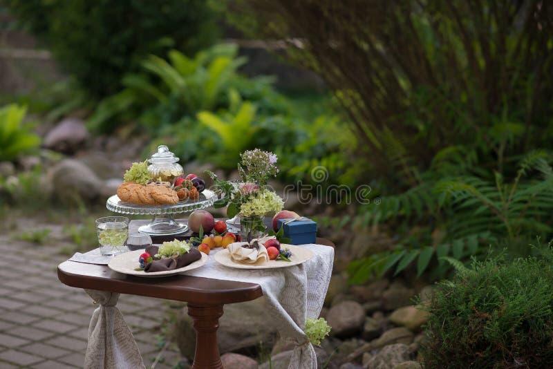 与欢乐款待的表和桌布在夏天庭院里 免版税图库摄影