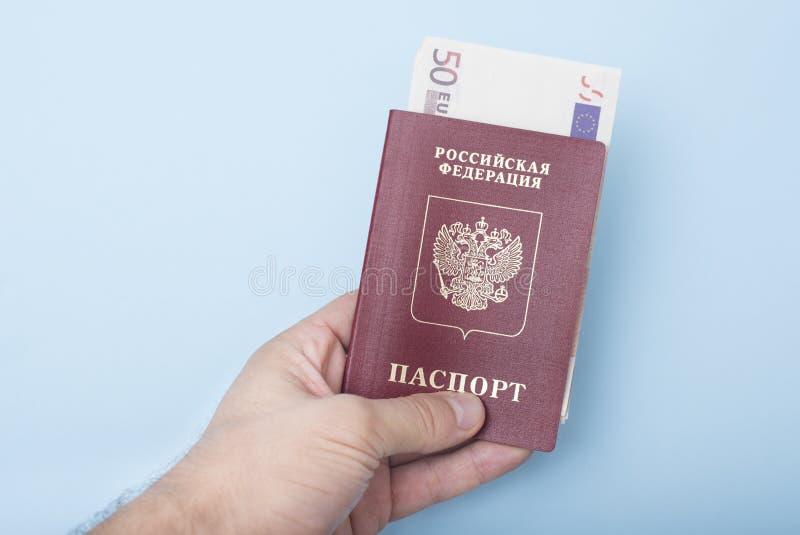 与欧元的俄国国际护照在人` s手上 蓝色 免版税库存照片