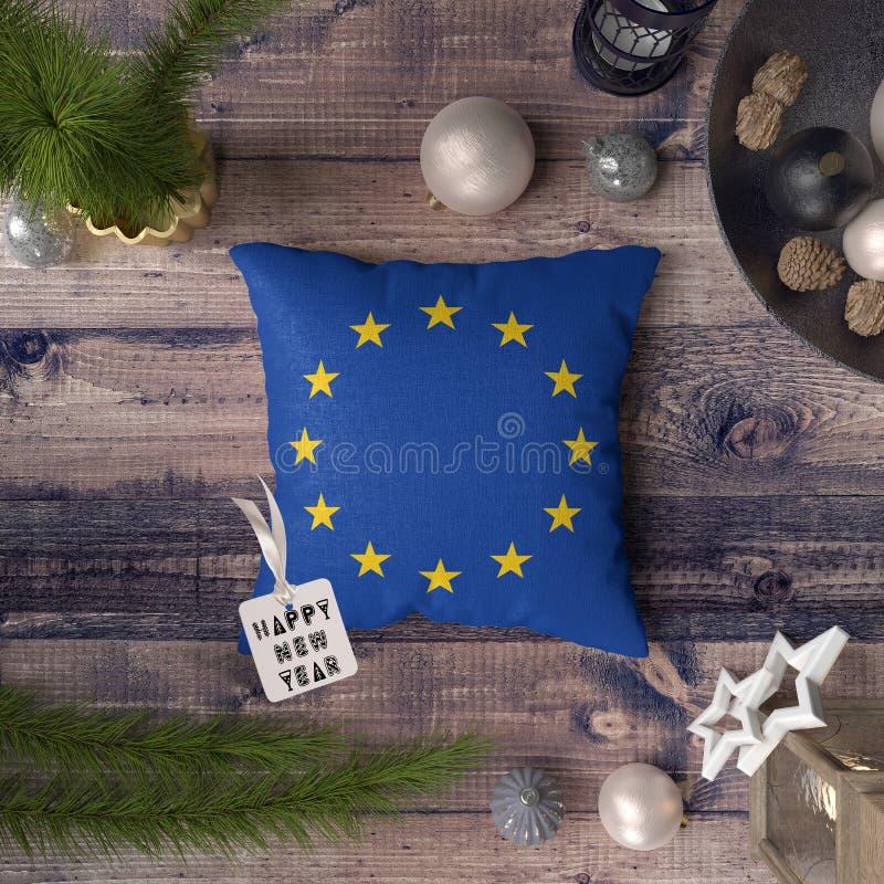与欧盟旗子的新年快乐标记在枕头 在木桌上的圣诞装饰概念与可爱的对象 免版税库存照片