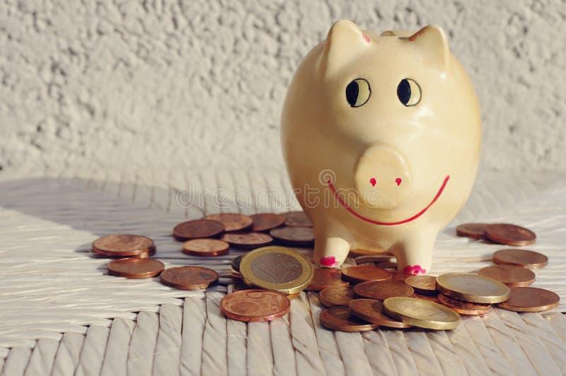 与欧洲硬币的猪moneybox在白色木背景 免版税库存照片