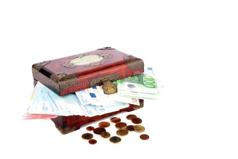 与欧洲钞票和硬币的老木胸口 免版税库存图片