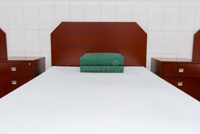 与正方形的整洁和整洁的床折叠了被子 图库摄影