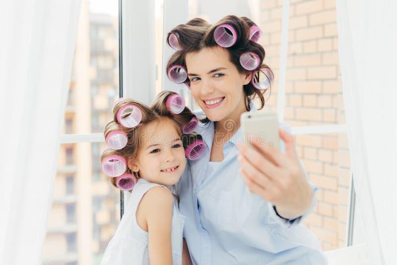 与正面表示,在她的母亲附近的迷人的微笑立场的可爱的小孩子,做与现代手机的selfie,姿势a 库存照片