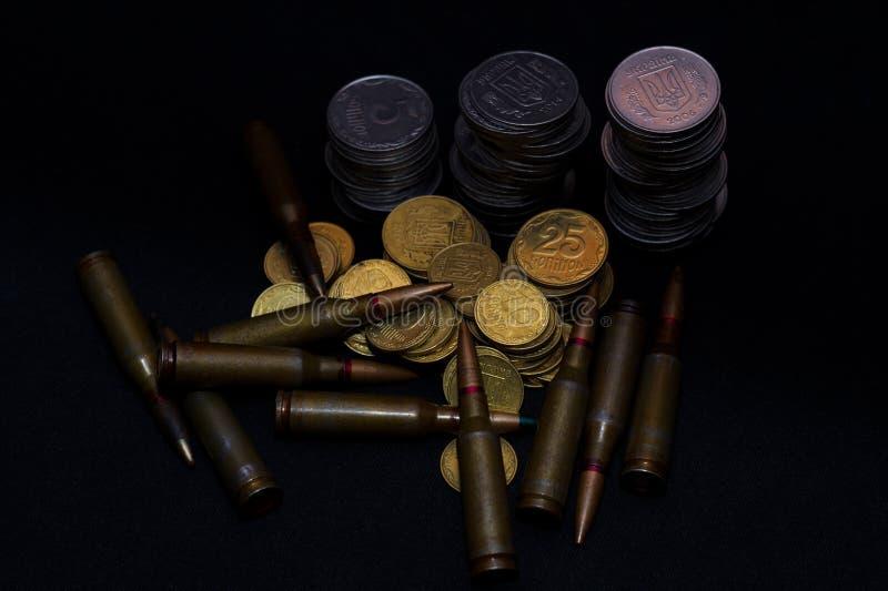 与步枪军用弹药的乌克兰小硬币在黑背景 象征金钱的战争 库存照片